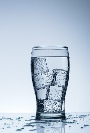 Cold purified water in the glass with bubbles and reflection on the wet background Stock Photo - 7325005