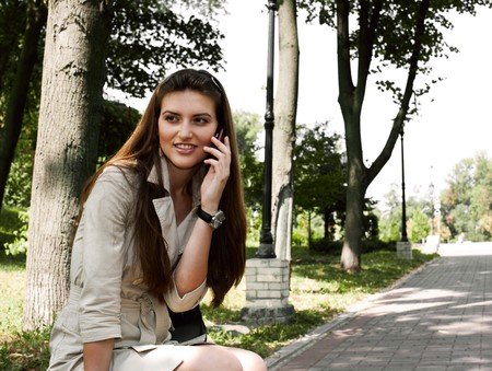 young beauty woman calling to someone on the the park bench Stock Photo - 7494049