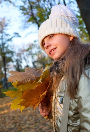 far away look: young girl with golden fallen mapple leaves in her hands