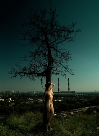 nude outdoors: loneliness in the city. urban scene with naked girl