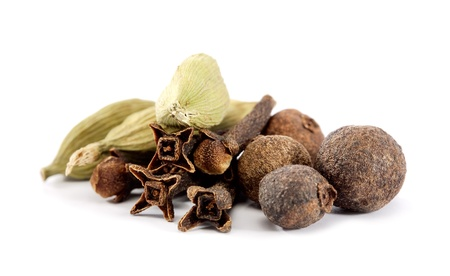 closeup of cloves, cardamon and allspice over white background photo