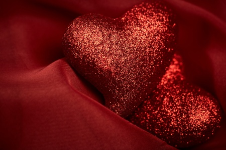 two object: abstract Valentines backgrounds over red textile with tho hearts
