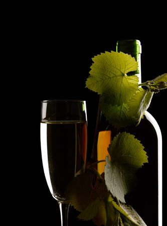 Wine glass with bottle. Still life against black backgrounds photo