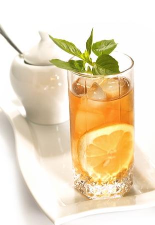 bebidas frias: El t� negro fr�o con gotas de lim�n, hielo y agua en la superficie del vidrio Foto de archivo