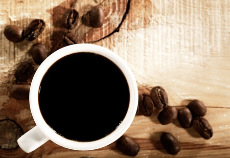 capuccino: Coffee beans with white cup over wooden desk, view from above Stock Photo