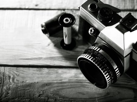 Vintage 35 mm film photo camera over wooden desk photo