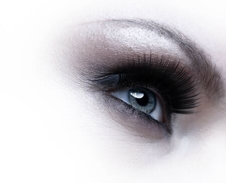 Human eye with eyelashes over white background photo