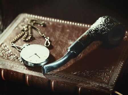 Abstract retro still life with old leather covered book and watch photo