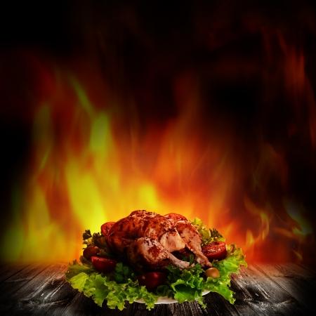 pollos asados: Pollo a la plancha sobre la ensalada en la mesa de madera