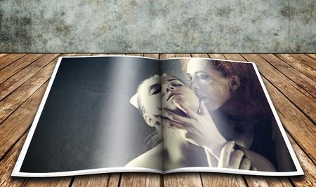 Vampires kiss. Glossy magazine over wooden desk photo