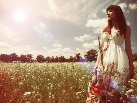 Beauty young woman walking around the summer meadow photo