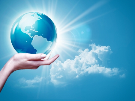 earth core: Female arm holding Earth  globe against blue skies, environmental backgrounds