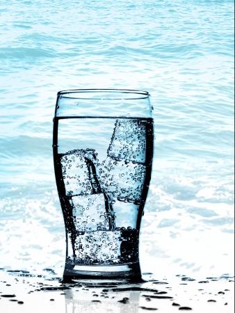 purified: Agua purificada fr?a en el cristal con burbujas y la reflexi?n sobre el fondo mojado