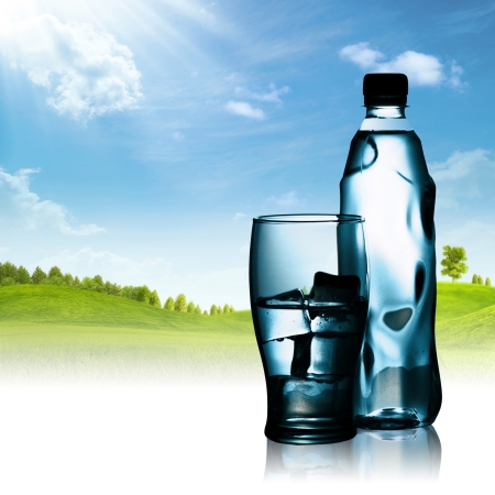 Spring mineral water bottled with glass and ice against natural landscape photo