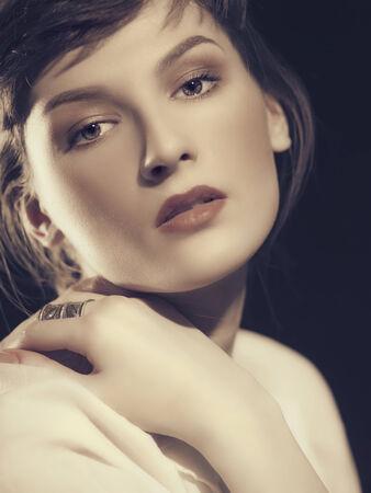 Vogue. Female portrait against dramatic dark  photo