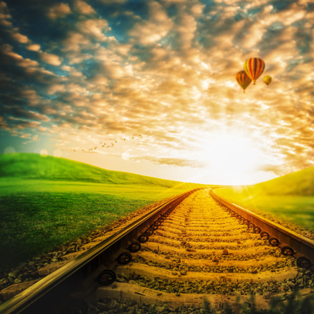 train tracks: Railroad through the green valley, under blue skies with air balloons Stock Photo