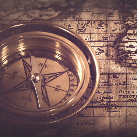 Old nautical compass over the map, abstract retro still life photo