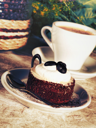 Coffee cup and tasty cake on the desk, food still life for your design photo