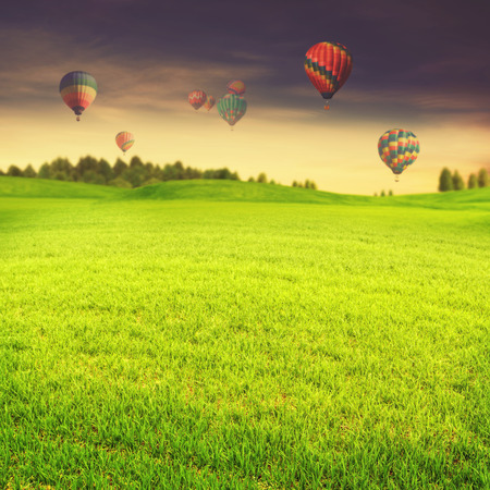 Hot air balloons over green summer meadow, abstract travel backgrounds photo