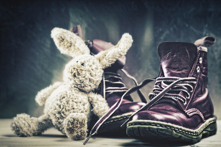 trampled: Baby boots and plush rabbit toy close up shot.  Grungy backgrounds Stock Photo