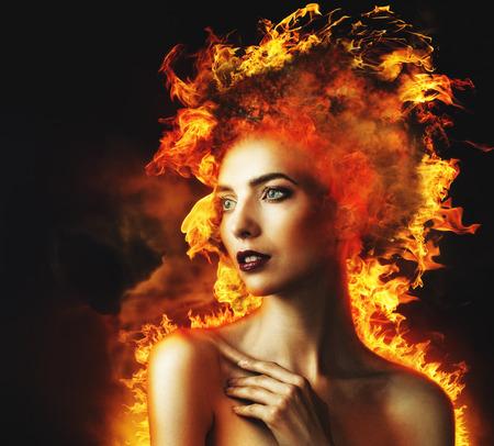 firestarter: Firestarter. Abstract beauty portrait with burning flame as part of human Stock Photo