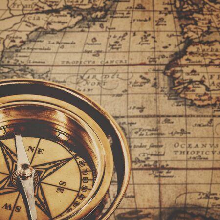 descubridor: Compás de cobre amarillo retro sobre antiguos mapas de papel, fondos de aventura