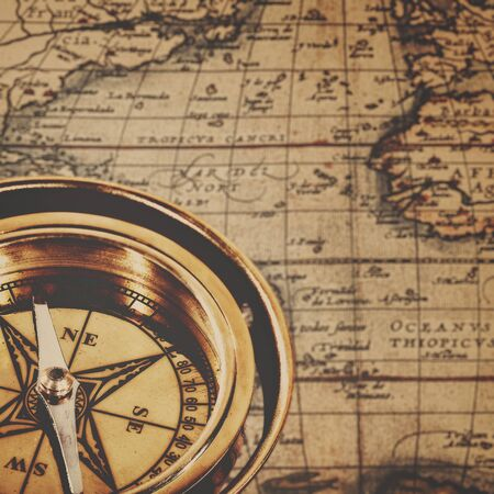 retro backgrounds: Retro brass compass over antique paper map, adventure backgrounds Stock Photo