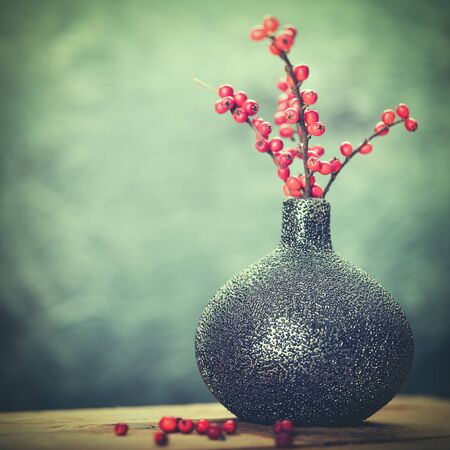december: Abstract still life with ceramic vase and red berries