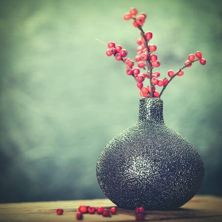 diciembre: Resumen de bodegón con jarrón de cerámica y bayas rojas Foto de archivo