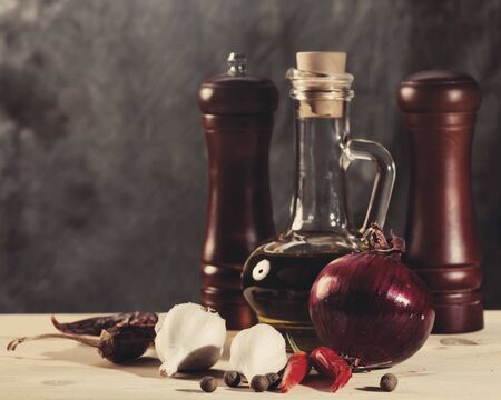 Cuisine still life with olive oil, spices and onion