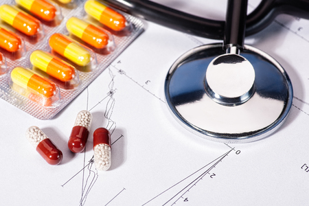 Abstracte geneeskunde achtergronden met pillen, stethoscoop over hart diagram