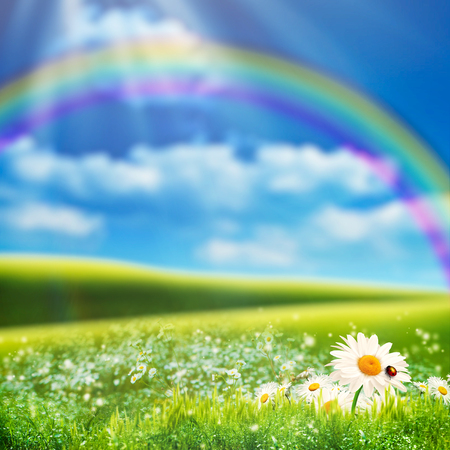rainbows: Dreamy natural landscape with green hills under blue skies and funny rainbow Stock Photo
