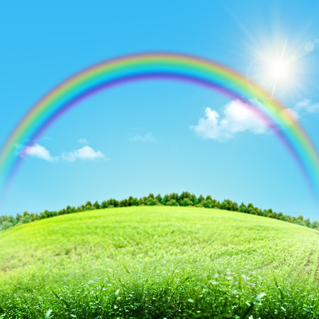 Dreamy natural landscape with green hills under blue skies and funny rainbow Stockfoto