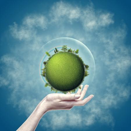 Tierra verde en la mano femenina contra fondos azules, diseño ecológico