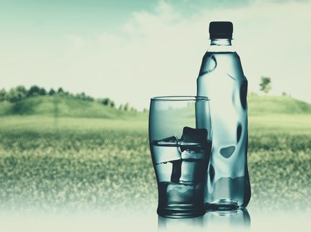 Bottled spring mineral water against abstract natural backgrounds Stock Photo