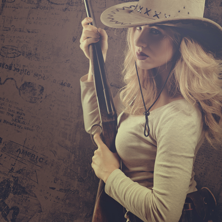 Wild west. Female portrait of cowgirl with vintage hunting rifle 版權商用圖片