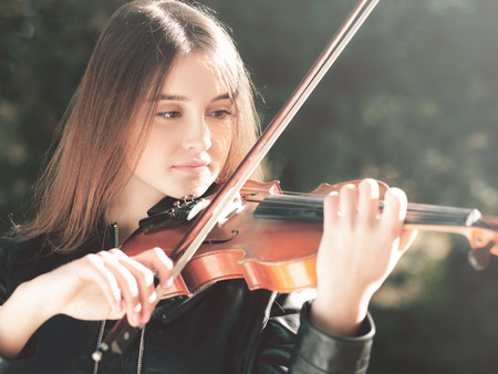 Young beauty musician playing his violin, urban female portrait
