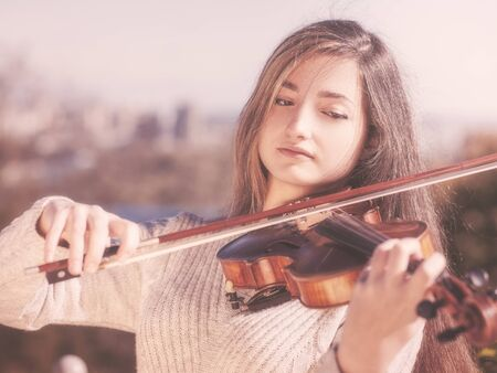 musico: Young beauty musician playing his violin, urban female portrait