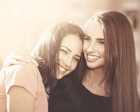amistad: Amistad, par de chicas jóvenes sonriendo, retrato femenino urbano Foto de archivo