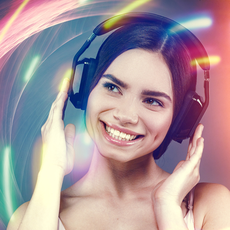phono: Beauty female portrait with headphones and lens flares as background Stock Photo