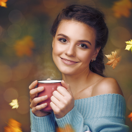 Beauty young woman with cup of tea against autumnal backgrounds Standard-Bild