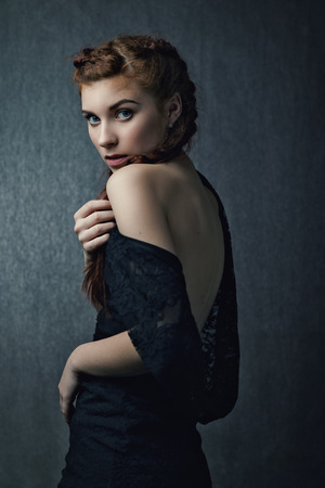 Beautiful red head girl looking at camera, studio female portrait