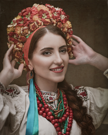 Ethno Beauty. Beautiful young woman in traditional ukrainian dress and crown Standard-Bild