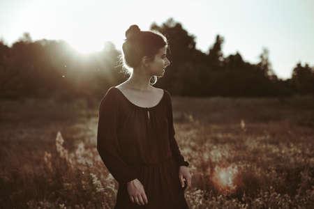 Summer Portrait. Young adult woman walking around meadow Standard-Bild