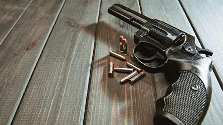Retro still life. Handgun and cartridges over vintage wooden desk Standard-Bild