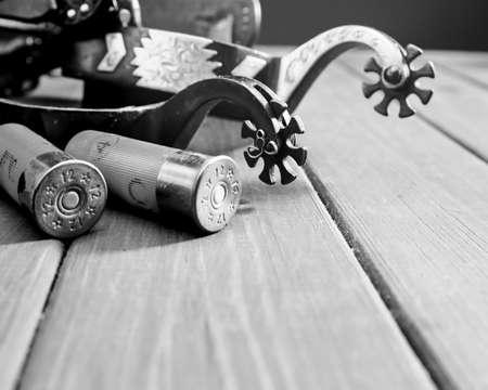 Retro still life. Cartridges, and spurs over vintage wooden desk Standard-Bild