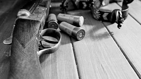 Retro still life. Cartridges, rifle and spurs over vintage wooden desk Standard-Bild