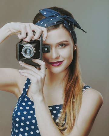 Photographer. Female Pinup Portrait. Young adult woman posing with vintage photo camera Standard-Bild