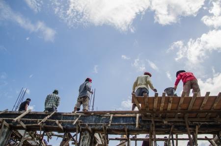 veiligheid bouw: Arbeiders worden bulding huis Redactioneel