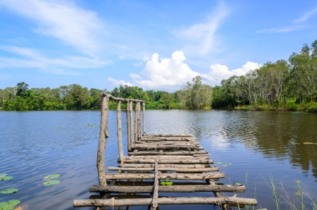The wood bridge in the lake with blue sky background photo